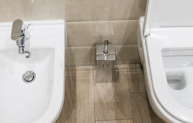 Dettagli del bidet e della toilette ceramici bianchi con la spazzola della toilette in bagno moderno fotografie stock libere da diritti