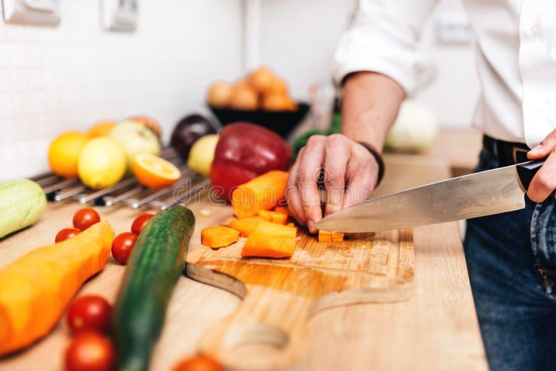 Dettagli del maschio bello che tagliano le verdure a pezzi con il coltello Cuoco professionista che prepara insalata immagini stock libere da diritti
