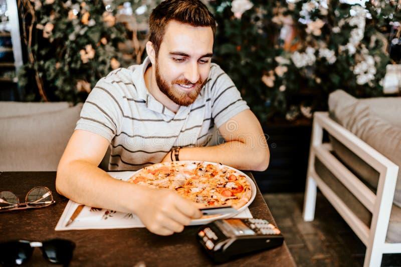 Dettagli del pagamento cred della carta al ristorante Uomo facendo uso della carta di credito e telefono per il pagamento del con immagine stock libera da diritti