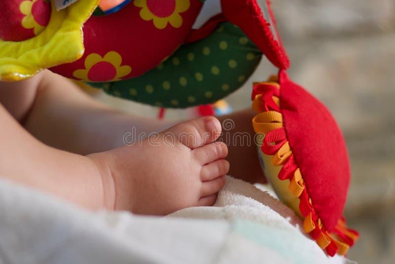 Dettagli del piede del neonato che dormono vicino ai giocattoli multicolori immagini stock