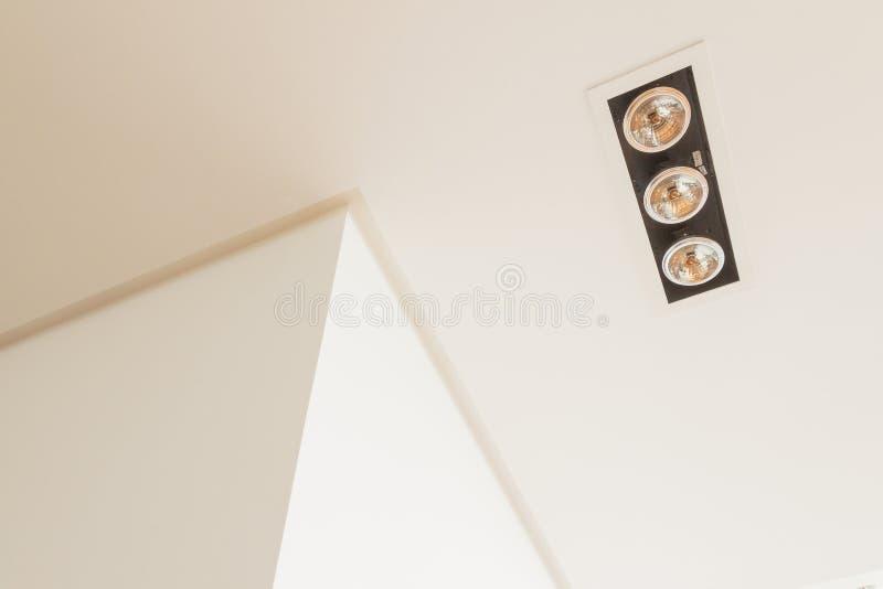 Dettagli della costruzione: lampade, scanalatura del soffitto e griglie di aria d'angolo della parete sul soffitto falso fotografia stock