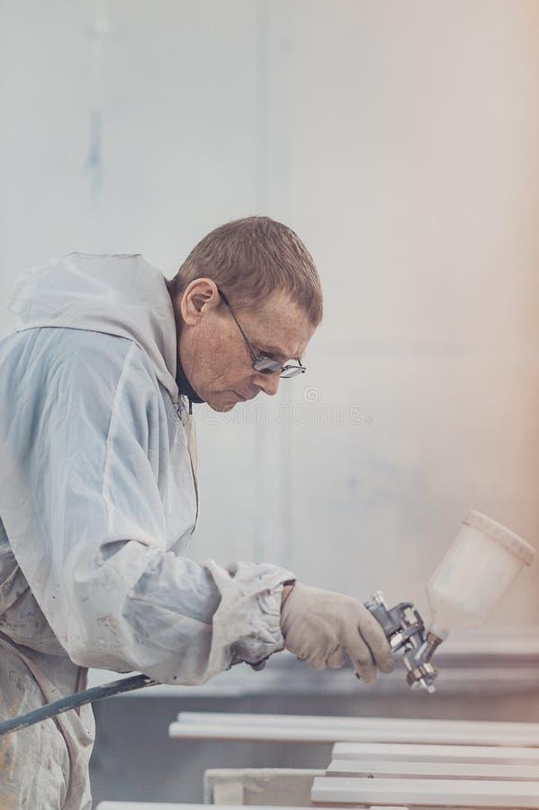 Dettagli della mobilia della pittura dell'uomo Lavoratore che per mezzo della pistola a spruzzo fotografie stock libere da diritti
