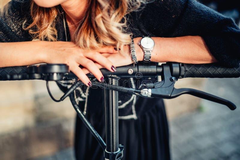 Dettagli della ragazza che per mezzo del motorino elettrico Dettagli delle mani e della ruota fotografia stock