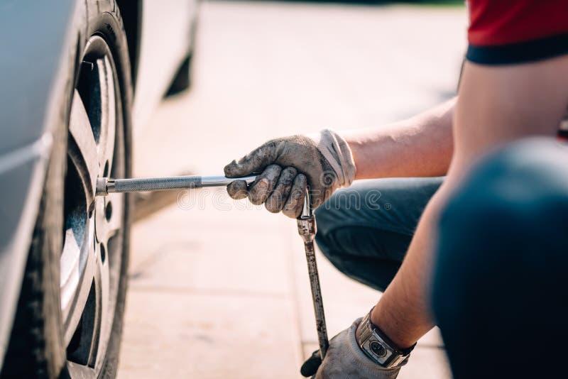 Dettagli delle gomme cambianti del meccanico, lavorando nell'officina e facendo le riparazioni sulle automobili fotografia stock