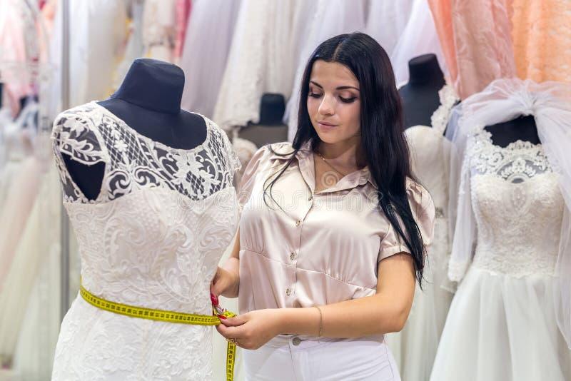 dettagli di misurazione del venditore della donna del vestito da sposa fotografie stock