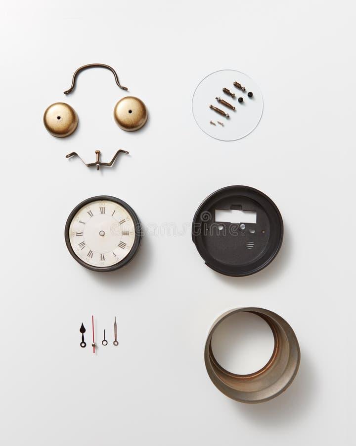 Dettagli differenti di vecchio orologio meccanico e di un fronte sorridente fatti dai dettagli su un fondo grigio con spazio per fotografie stock libere da diritti
