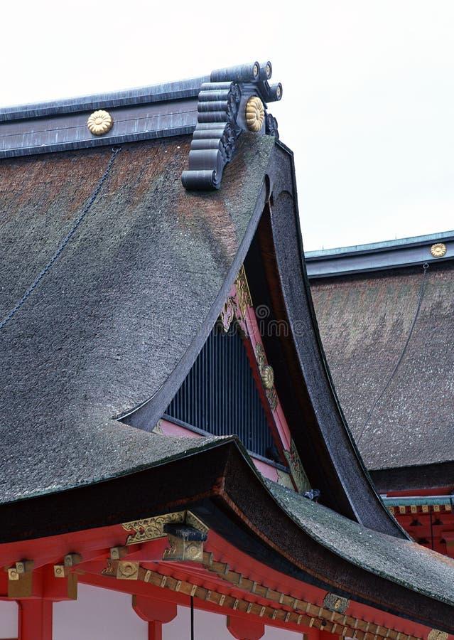 Dettagli giapponesi del tetto del santuario con il fondo nero e rosso delle sculture immagini stock