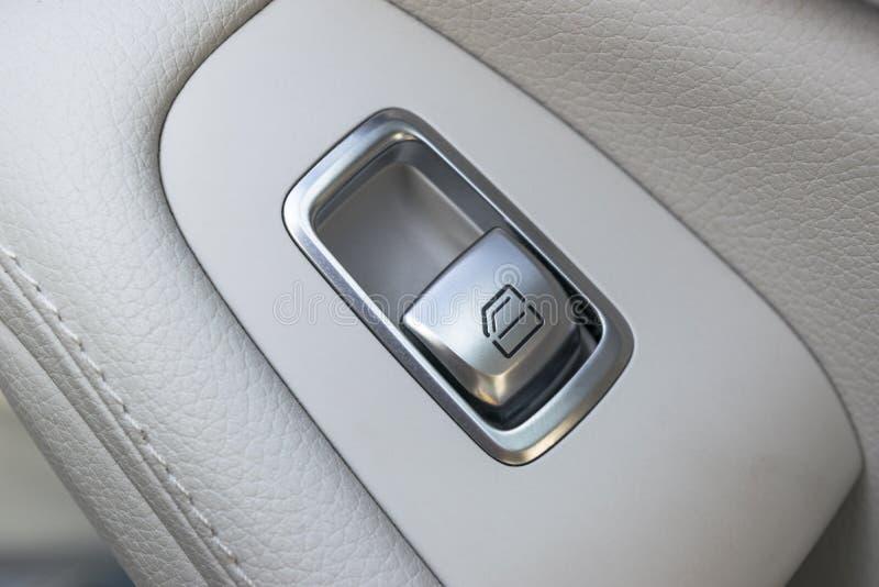 Dettagli interni del cuoio bianco dell'automobile della maniglia di porta con i comandi e gli adeguamenti delle finestre Comandi  immagine stock