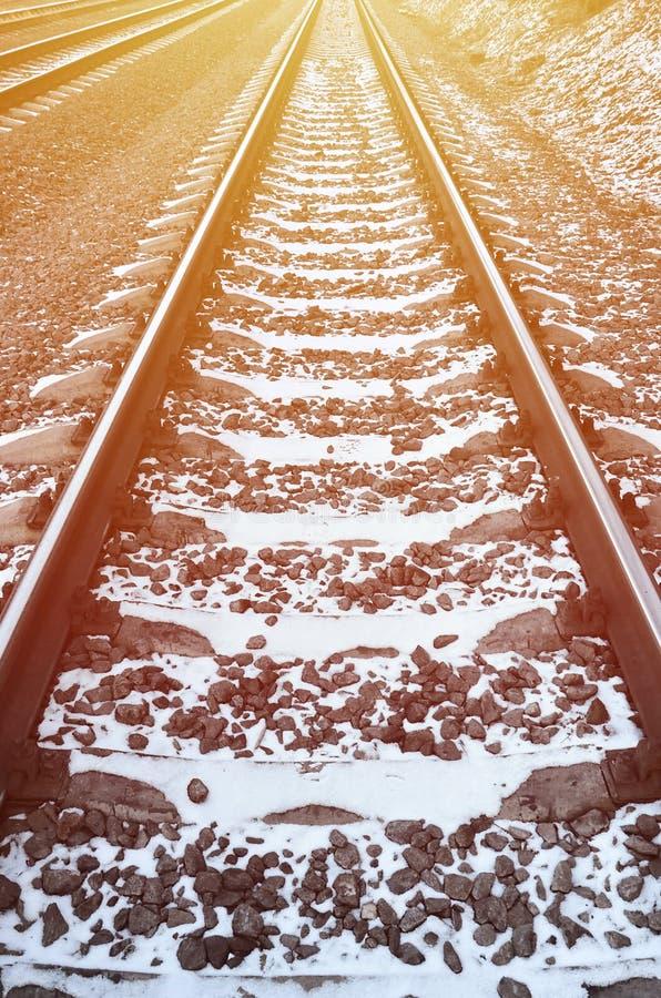 Dettaglia la ferrovia russa nevosa dell'inverno nell'ambito di luce solare luminosa Le rotaie e le traversine nell'ambito di dice immagine stock libera da diritti