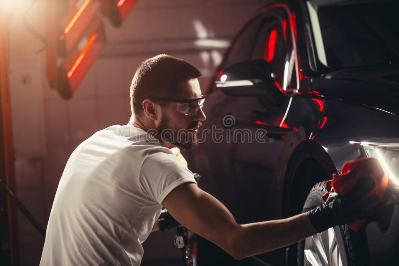 Dettagliare dell'automobile - l'uomo giudica il microfiber disponibile e lucida l'automobile fotografie stock