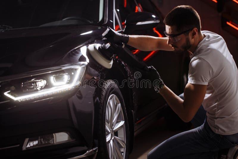 Dettagliare dell'automobile - uomo con il lucidatore orbitale nell'officina riparazioni automatica Fuoco selettivo immagine stock libera da diritti