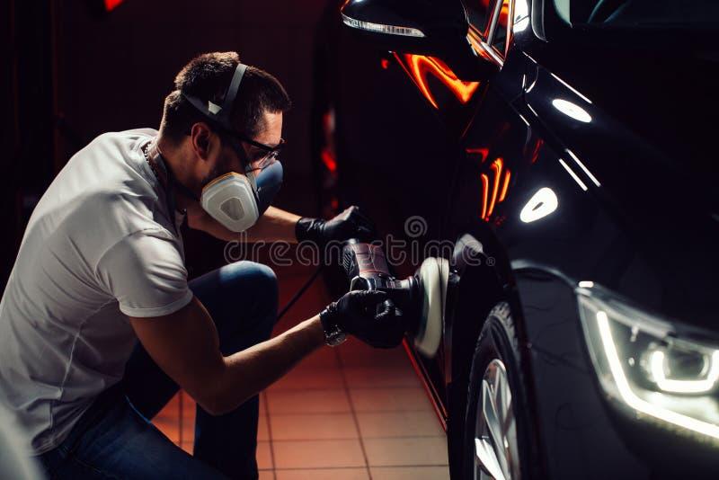 Dettagliare dell'automobile - uomo con il lucidatore orbitale nell'officina riparazioni automatica Fuoco selettivo immagini stock