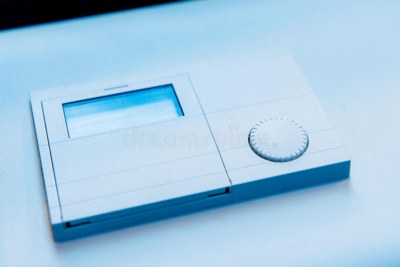 Dettaglio del primo piano del termostato su fondo blu immagini stock libere da diritti
