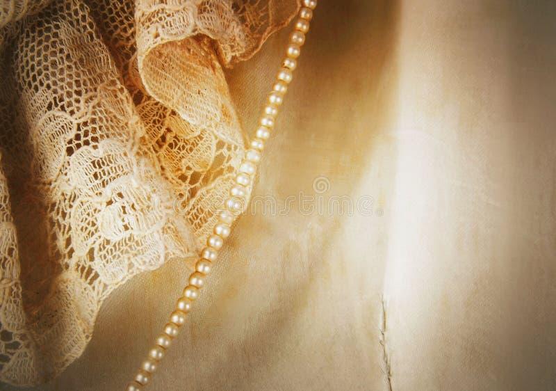 Dettaglio del primo piano di raso d'annata e del vestito da sposa dal pizzo con un filo delle perle minuscole fotografie stock libere da diritti