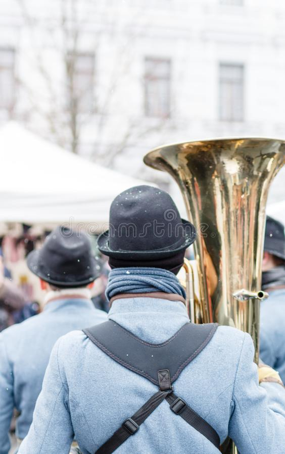 Dettaglio del primo piano di retro weared stando indietro soldato con la grande tuba d'ottone e l'altro fondo dei soldati immagine stock
