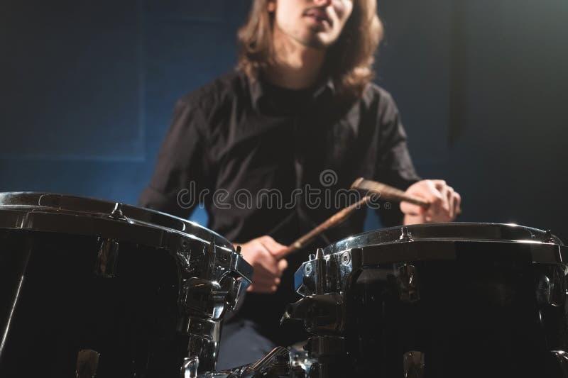 Dettaglio del primo piano di un insieme del tamburo contro un batterista sfuocato vago con i bastoni del tamburo fotografia stock libera da diritti
