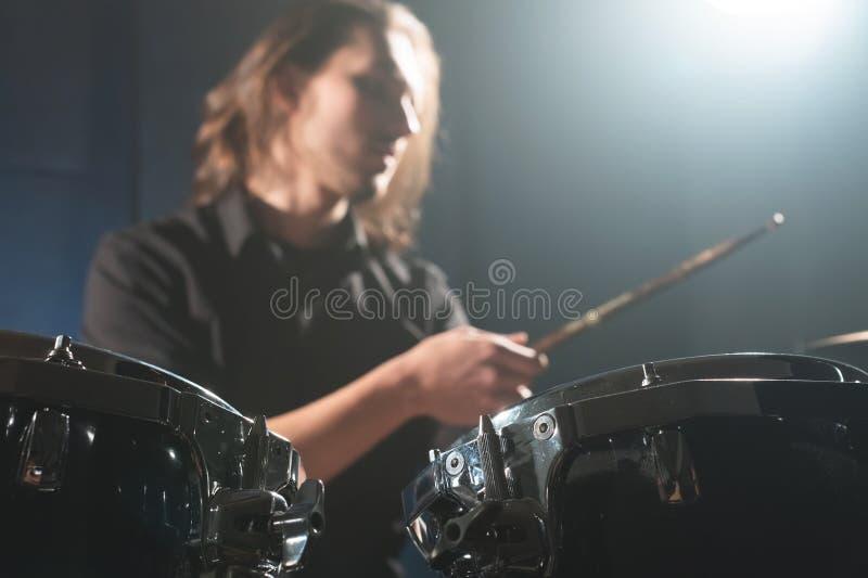 Dettaglio del primo piano di un insieme del tamburo contro un batterista sfuocato vago con i bastoni del tamburo immagine stock libera da diritti