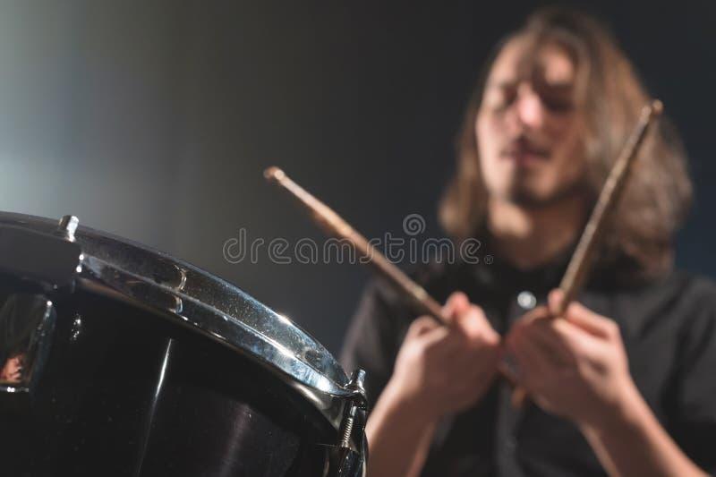 Dettaglio del primo piano di un insieme del tamburo contro un batterista sfuocato vago con i bastoni del tamburo fotografie stock