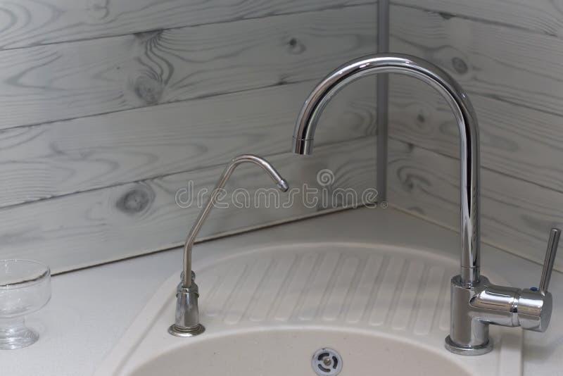 Dettaglio del primo piano di un lavandino di cucina del metallo con due rubinetti in un interno del lusso immagine stock