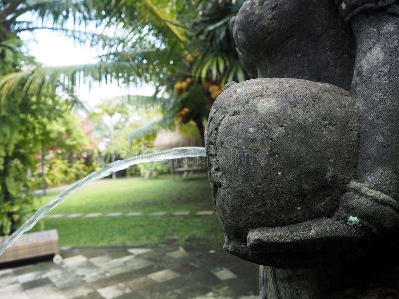 Dettaglio della brocca di statua della fontana in un giardino in Bali, Indonesia immagini stock libere da diritti