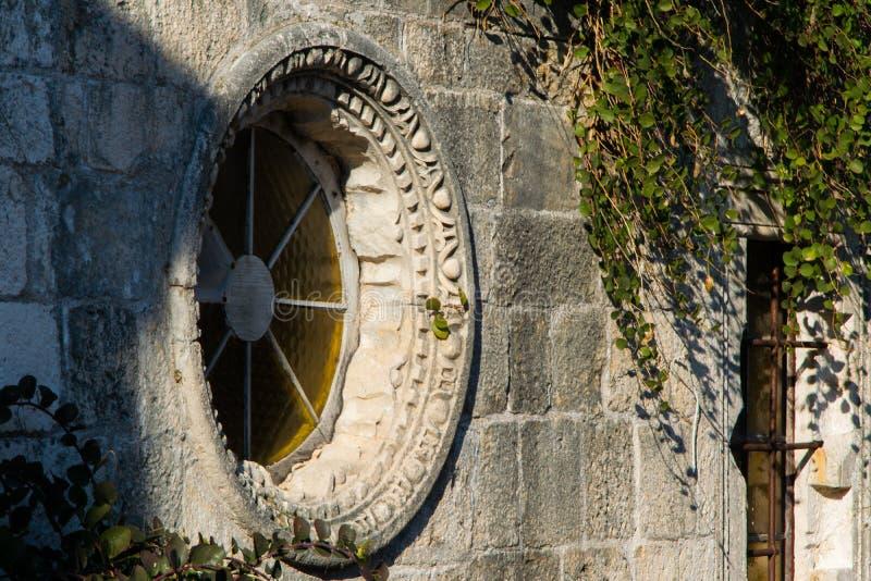 Dettaglio della finestra rotonda su una parete di pietra antica - vecchia città Budua fotografia stock libera da diritti