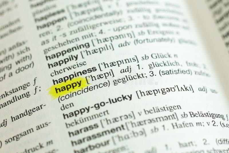 Dettaglio della parola inglese felice e della sua traduzione tedesca fotografie stock libere da diritti