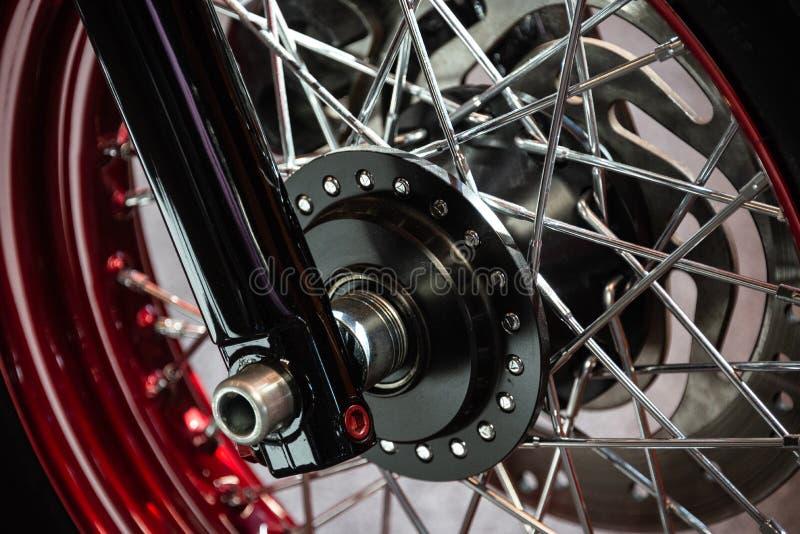 Dettaglio della ruota nera di un motociclo su misura cromato con le ruote rosse e d'argento fotografia stock