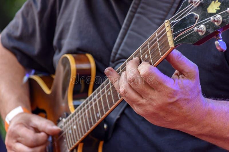Dettaglio delle mani di guitarrist e della sua chitarra elettrica nera immagine stock