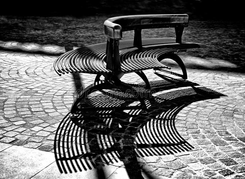 Dettaglio di architettura, banco nel parco della città, banco nel quadrato di città in bianco e nero, ombre del banco, frammento  fotografia stock libera da diritti