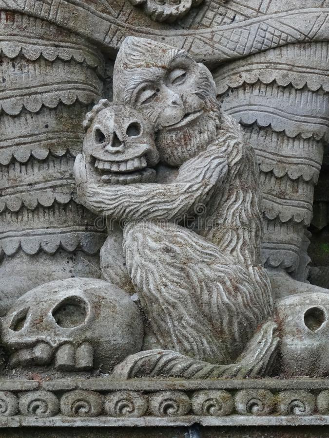 Dettaglio di pietra divertente di una scimmia che tiene un cranio immagine stock