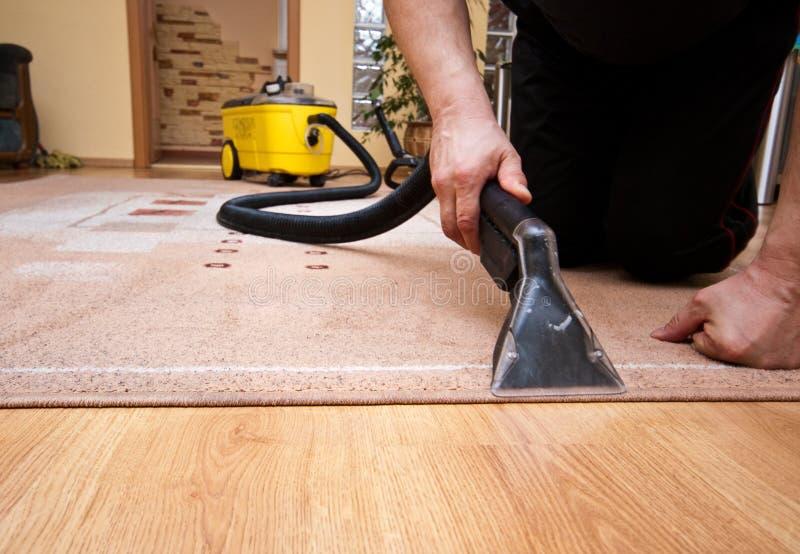 Dettaglio di servizi del tappeto di pulizia con la macchina di giallo fotografia stock libera da diritti