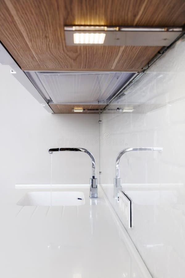 Dettaglio di un lavandino di cucina rettangolare del progettista con il rubinetto di acqua del cromo immagini stock