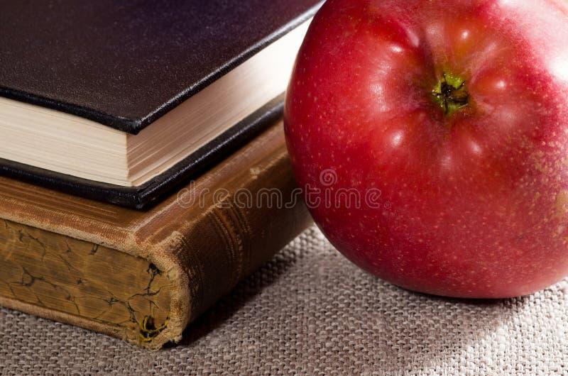 Dettaglio di vecchi libri nella mela di rosso del primo piano e della copertina dura immagine stock libera da diritti