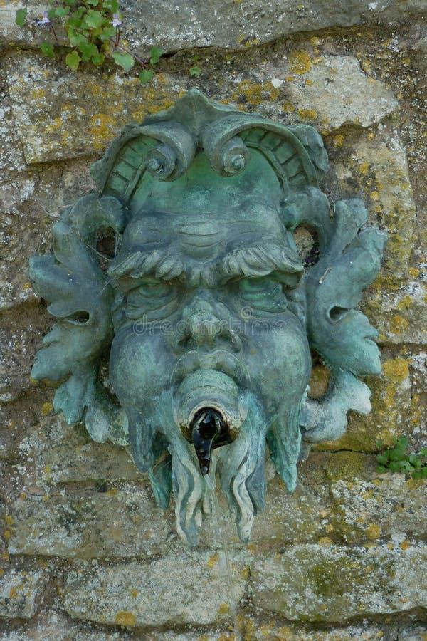 Dettaglio di vecchia maschera di greenman sulla parete di pietra immagine stock libera da diritti