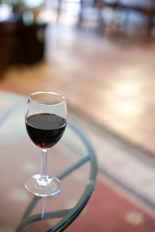dettaglio di vetro con vino rosso sulla cima una tavola fotografie stock libere da diritti