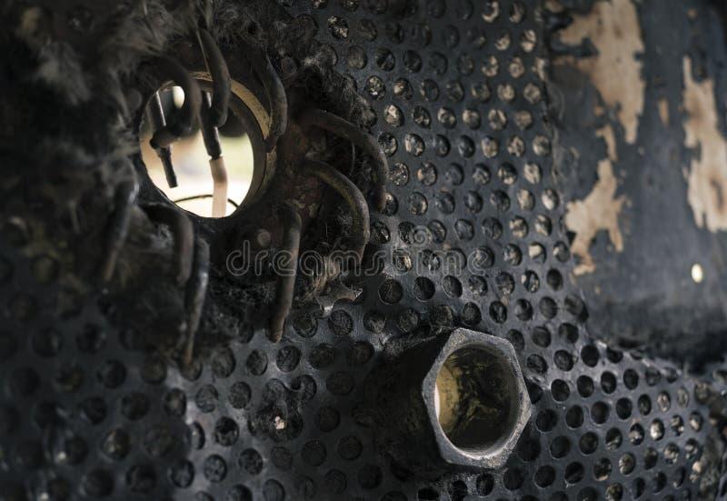 Dettaglio industriale sbiadito ed invecchiato - foro, reticolato con i fori di spillo arrotondati, dado del metallo fotografia stock