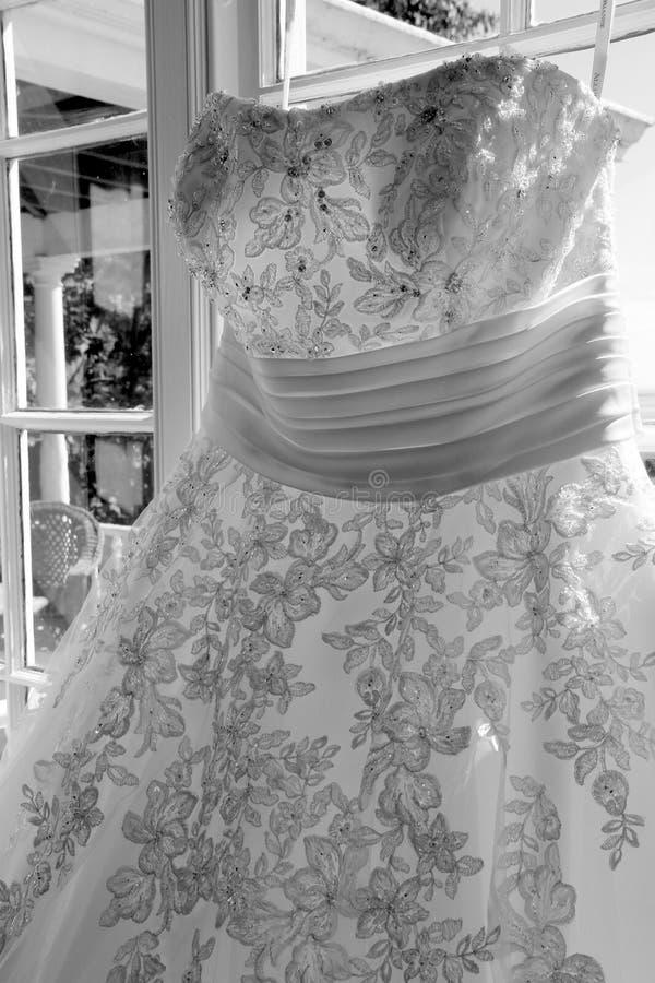 Dettaglio splendido di bordare del vestito da sposa che appende nella finestra fotografia stock libera da diritti