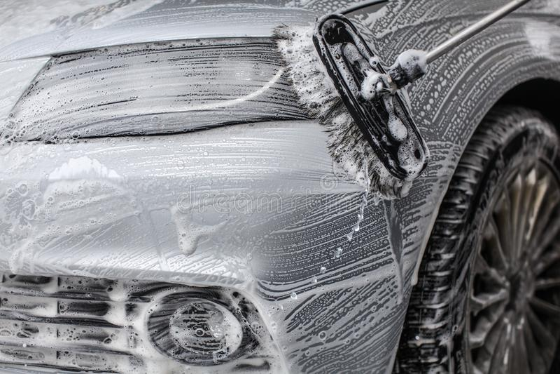 Dettaglio sulla parte anteriore dell'automobile coperta nella schiuma del sapone, lavata di spazzola dentro immagini stock libere da diritti