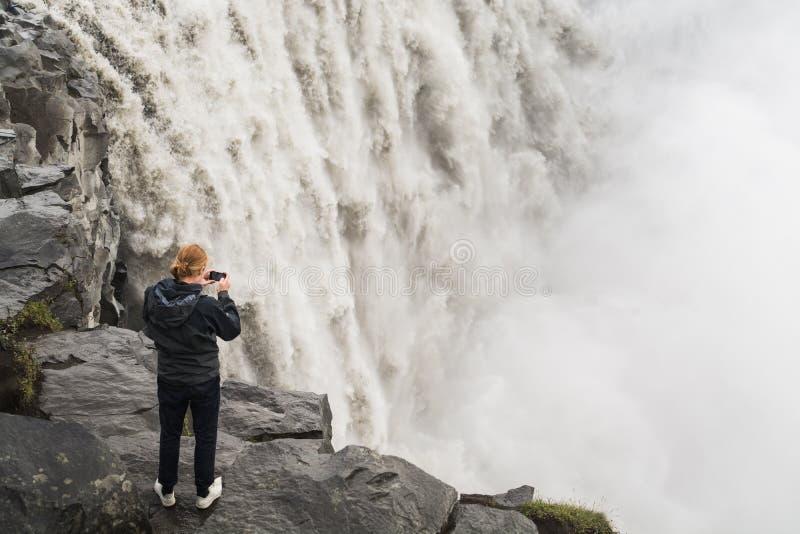 DETTIFOSS ISLAND - AUGUSTI 2018: Man i svart tagande bild av vattenfallet på klippkanten i den Vatnayokull nationalparken arkivbild