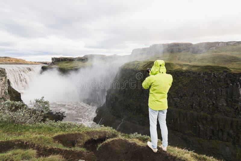 DETTIFOSS ISLAND - AUGUSTI 2018: Man som tar bilden av vattenfallet på klippkanten i den Vatnayokull nationalparken royaltyfri foto