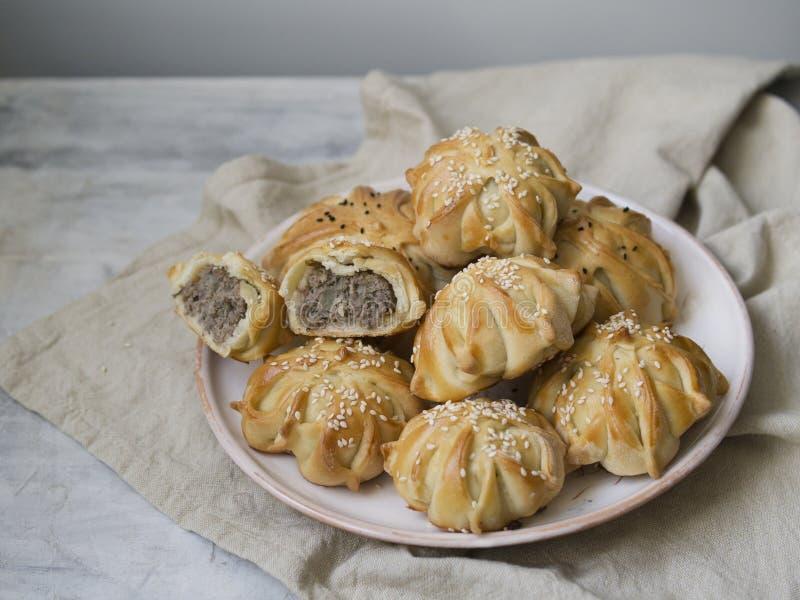 Deu forma interessantemente ? mini torta da carne fresca Tortas deliciosas do samosa com carne na placa no fundo cinzento Parte d fotografia de stock