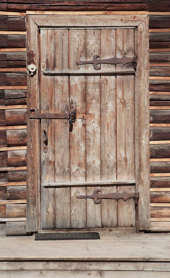 Deur in muur van een oud logboekhuis stock afbeeldingen