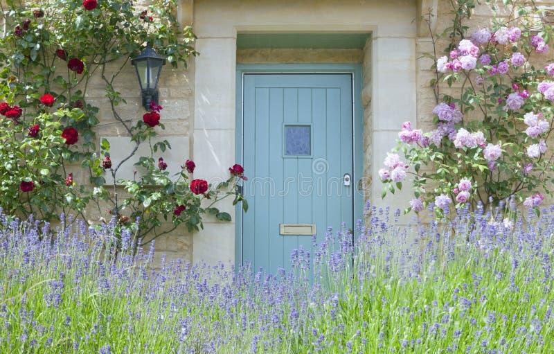Deuren in een Engels plattelandshuisje met rozen, lavendelbloemen royalty-vrije stock foto