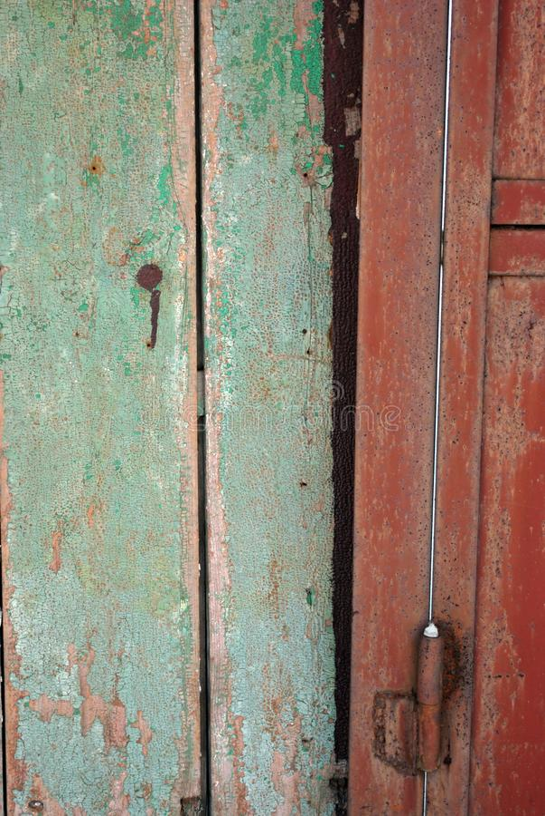 Deurkader met sjofele groen en deur met handvat van donkerrode kleur, grunge textuur royalty-vrije stock foto