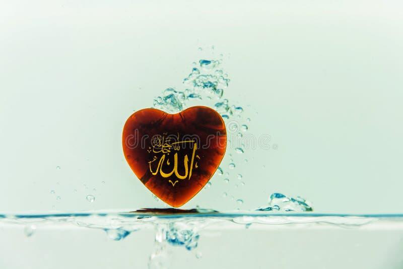 deus do ` de allah do ` do Islã com respingo da água do símbolo com bolhas do ar, no fundo branco imagem de stock