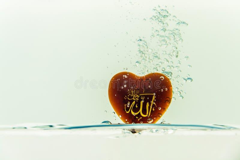 deus do ` de allah do ` do Islã com respingo da água do símbolo com bolhas do ar, no fundo branco fotos de stock royalty free
