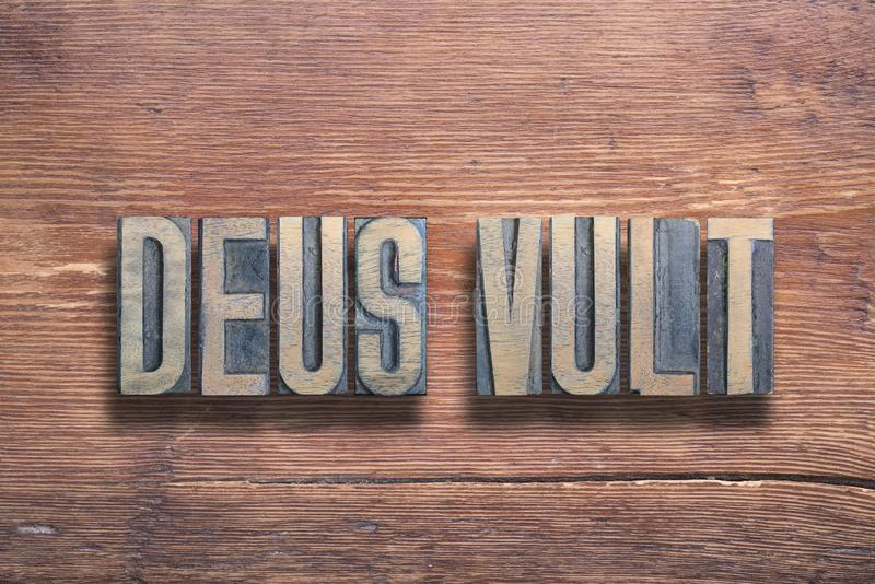 Deus vult wood. Deus vult ancient Latin saying meaning - God wills, combined on vintage varnished wooden surface royalty free stock photography