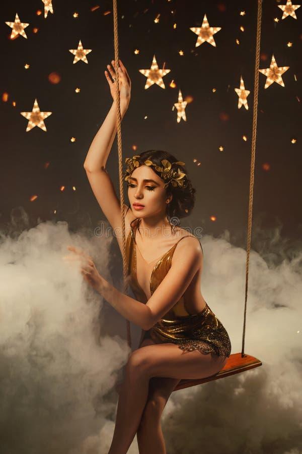 Deusa dourada da noite, moça de surpresa com bois escuros e uma grinalda, em um vestido de cocktail curto com uma malha imagem de stock royalty free