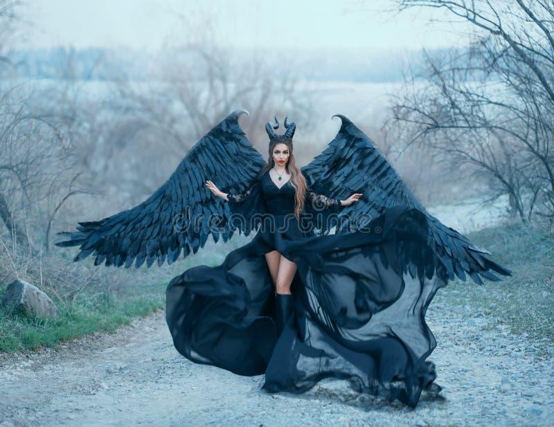 A deusa escura lindo de encantamento controla o vento, a bainha das ondas do fluxo de ar e o trem longo do vestido preto leve com imagens de stock