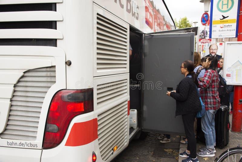 Deutsch- und Ausländerreisendleute empfangen Gepäck vom Vorratsraum des Busses lizenzfreie stockbilder